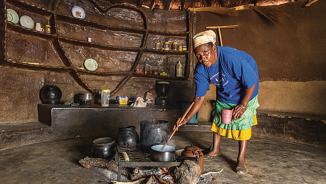 Woman in cooking over an open fire in a hut.
